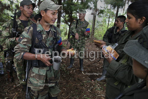 Members of the FARC guerilla taking cover under trees to avoid being seen by the army, receive their food ration. - Boris Heger - 2010-06-26