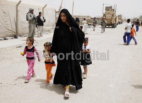Internal displaced people (IDPs) walk past American troops at a makeshift camp near Chikook suburb of north-west Baghdad, Iraq, July 23, 2009. - Boris Heger - 2009-07-23