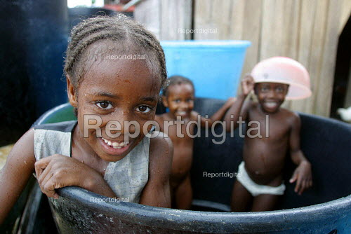 Children are having a bath at a displaced people accommodation center, in Quibdo, Choco region, Colombia, February 2004. There are an estimated 3 million people displaced by conflict with guerrilla groups. - Boris Heger - 2006-08-20