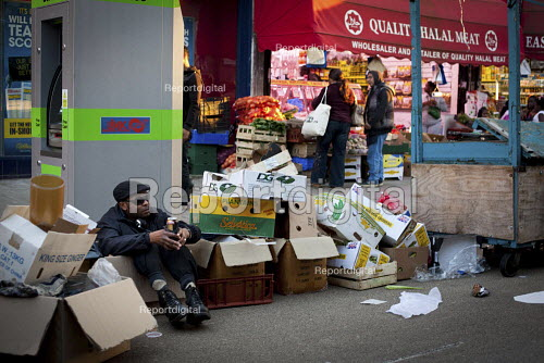 A man rests in a box with a can of beer, East Street Market, Walworth, London. - Connor Matheson - 2012-10-06