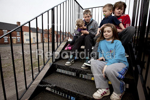 Young children sitting on the steps at the back of a local pub with boarded up houses in the background. Goldthorpe, South Yorkshire. - Connor Matheson - 2013-04-17