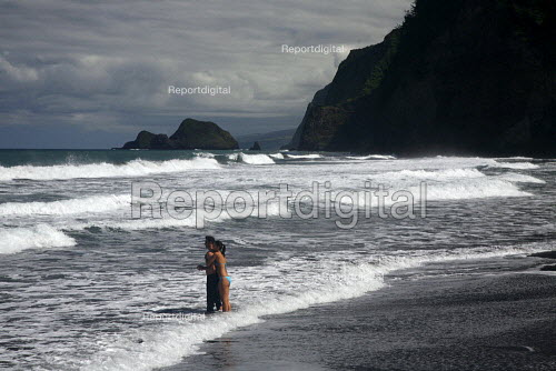 Lovers watch the surf at the beach in the remote Pololu Valley. The Hamakua coast on the windward side of the big island of Hawaii, Pacific Ocean. - David Bacon - 2010-02-13