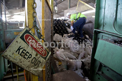 California- A young worker trying to free a jammed sorting belt. Workers sorting paper, cardboard, plastic, glass and metal from trash collected in Oakland. California Waste Solutions sorting facility. - David Bacon - 2015-02-19