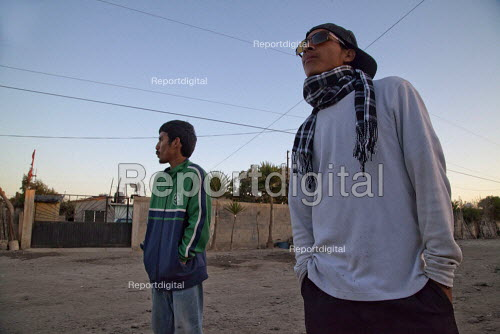 Vicente Guerrero, Mexico, Two cholos, or young people who have adopted a gang style, on the dirt street of The barrio of Nuevo San Juan Copala, The workers who live in this barrio are indigenous Triqui people. - David Bacon - 2015-06-05