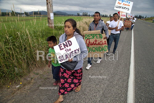 End the slavery. Migrant Mexican Farm workers demanding Trade Union recognition march to Sakuma Farms, a large berry grower in Washington. The workers and their supporters are demanding that the company bargain a contract with their union, Familias Unidas por la Justicia (FUJ). The workers are migrants from Oaxaca. Burlington, USA - David Bacon - 2015-07-11