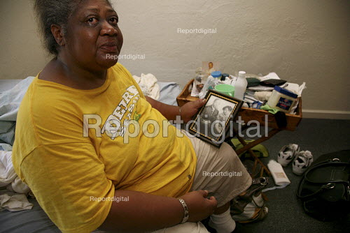 Tearful woman holding a photograph of her parents, living in a one room bedsit with her son. She is diabetic. They get food at a food pantry at St. Mary's Center supplied by the Alameda County Community Food Bank, Oakland, California, USA - David Bacon - 2009-09-11