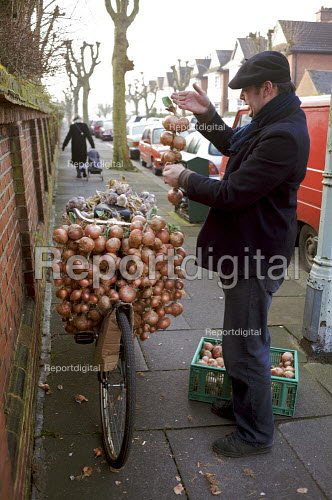 French Onion Seller and farmer, preparing his bike in traditional french fashion, to sell his onions in London - Duncan Phillips - 2009-02-01