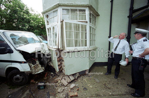 Crashed Vehicle, which left the North Circular Road London and hit a residential house. Pictured are a local authority Building surveyor and traffic policeman - Duncan Phillips - 2002-01-18