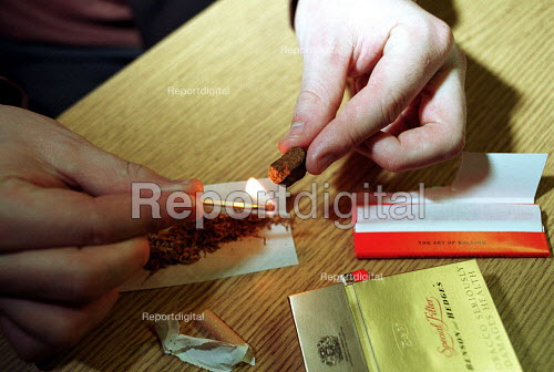 Smoker softening cannabis resin whilst rolling a joint - Duncan Phillips - 2002-01-31