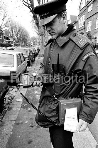 Local Authority Parking Attendant affixing a parking ticket to an illegally parked car. - Duncan Phillips - 2001-05-27