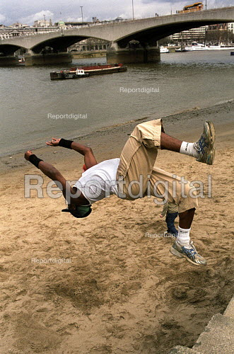 Young man practicing his jumps on a sandy beach beside the river Thames , London - Duncan Phillips - 2006-04-02