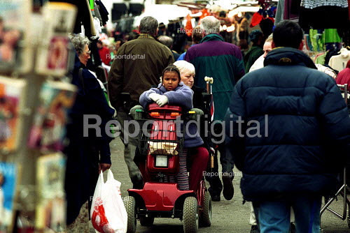 Shopper with child on electric buggy Chapel Market Islington - Duncan Phillips - 2001-12-05
