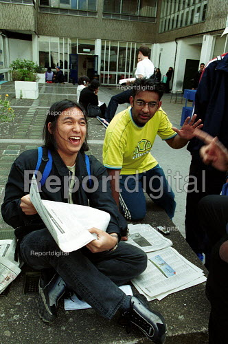 Students checking for University places in a national newspaper whilst celebrating their A level results - Duncan Phillips - 2002-10-24