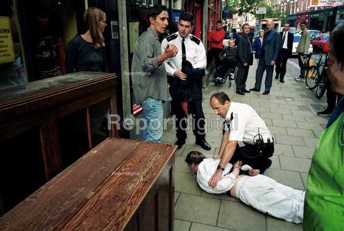 Police Officers apprehend a suspected shoplifter . Islington London - Duncan Phillips - 2000-07-22