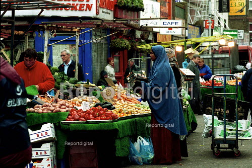 Shopper buying vegetables at a market stall Chapel Market. Islington, London - Duncan Phillips - 2001-12-05