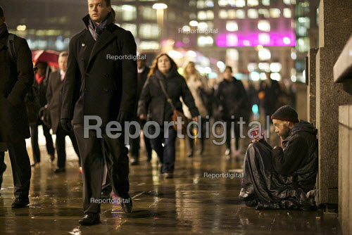 Homeless man begging in the rain, London Bridge, London. - Duncan Phillips - 2012-01-24