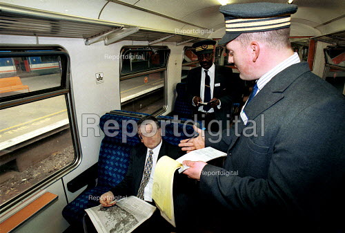 Revenue protection officers checking a passengers ticket.  The passenger is posed by an employee. - Duncan Phillips - 2002-11-28