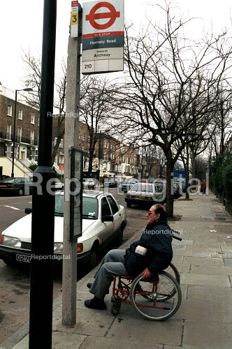 Disabled man in a wheelchair waiting at a bus stop for a bus with disabled access. - Duncan Phillips - 2002-12-02