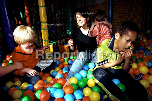 Mother with Autistic child playing in a ball pond indoor play centre. - Duncan Phillips - 1999-04-05