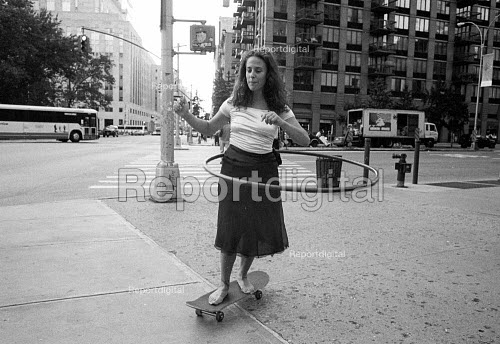 Woman spinning a hulahoop whilst Skateboarding. New York City. USA - Duncan Phillips - 2002-08-13