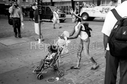Girl pushing a child in a pushchair, wearing a statue of liberty hat. New York City. USA - Duncan Phillips - 2002-08-13