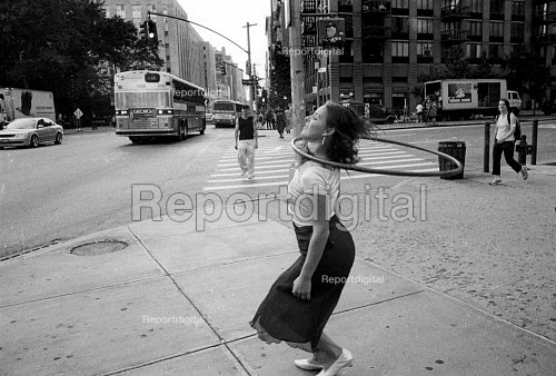 woman spinning a hula hoop aroung her neck in a New York Street. USA. - Duncan Phillips - 2002-08-13
