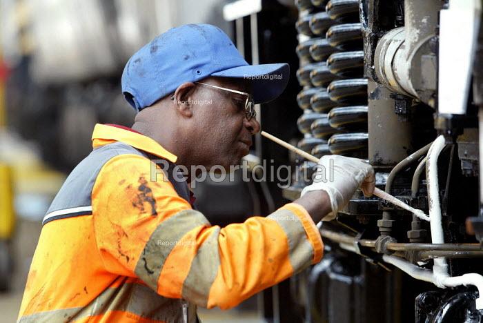 Engineer painting a locomotive. Maintenance Depot London - Duncan Phillips - 2003-07-18