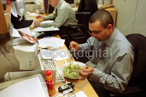 City Workers eating lunch at their desks. London - Duncan Phillips - 2001-05-21