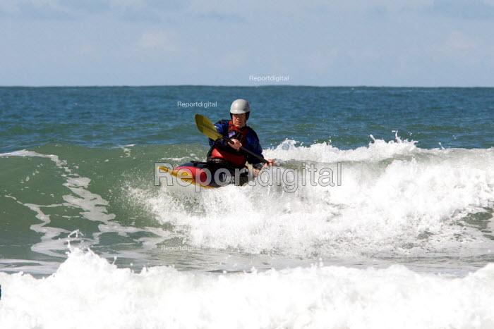 Elderly silver surfer surfing in canoe, Whitesands , Pembrokeshire, Wales - Duncan Phillips - 2009-04-11