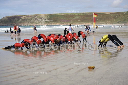 Surfing instructor with beginners, stretching, Surf School, Sennen Cove, Cornwall - Duncan Phillips - 2010-08-18