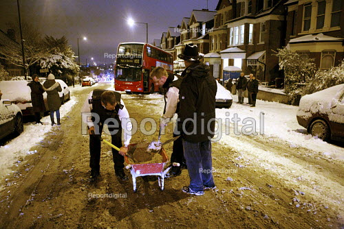 Severe cold weather brings disruption as heavy snow falls in London. Police officers and members of the public try to free standed bus with sand and grit to stop it slipping on the ice. - Duncan Phillips - 2010-12-18
