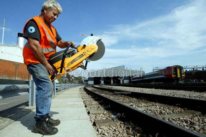 Track engineer holding angle grinder - Duncan Phillips - 2004-09-03