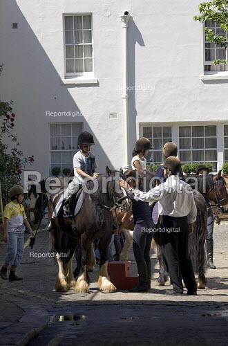 Children preparing for a Horse Riding lesson in a London Mews. - Duncan Phillips - 2005-07-12