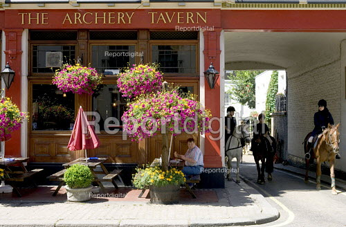 Children departing for a Horse Riding lesson from a London Mews next to a public house (The Archery Tavern) and a customer sitting outside. - Duncan Phillips - 2005-07-12