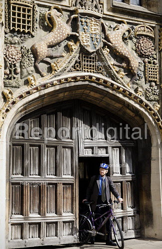 A lecturer emerging from the gate. Doorway to St John's College, Cambridge. Built in 1516 by the mason William Swayne. The statue above the door is of St. John the Evangelist the patron saint of the college. The rest of the carvings are the symbols and coat of arms of the Foundress of the college, Lady Margaret Beaufort. Her charges supporting the shield are mythical beasts called yale - chimera with the head of a goat, the body of an antelope and the tail of an elephant - Duncan Phillips - 2010-09-17