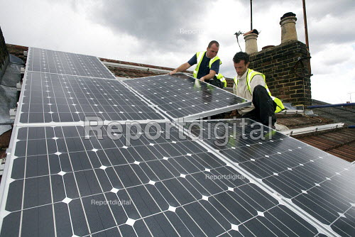 Contractors fixing solar panels to the roof of a terraced house, Barnet, London - Duncan Phillips - 2011-06-23