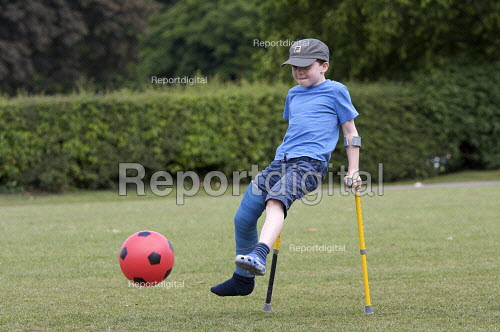 Child with broken leg in plaster playing football - Duncan Phillips - 2009-05-28