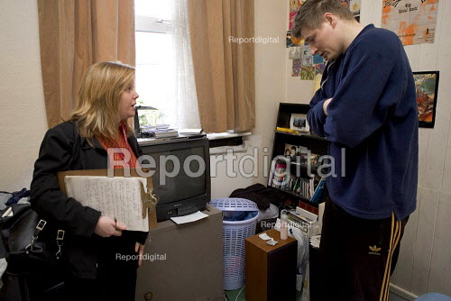 Environmental Health Officer conducting a heating assessment of a young man at home, who uses portable heaters to keep warm because their rented house has no central heating. - Duncan Phillips - 2006-03-22