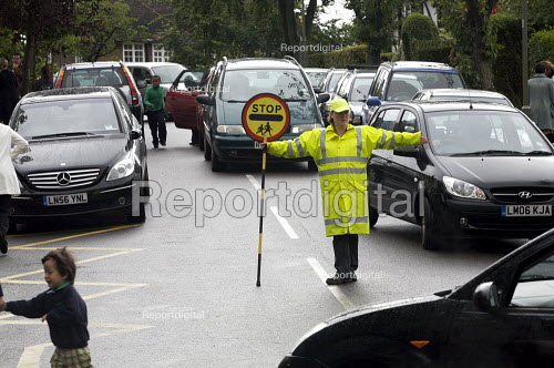 School Lollipop Lady stopping traffic so pedestrians can cross the road. London. - Duncan Phillips - 2007-06-29