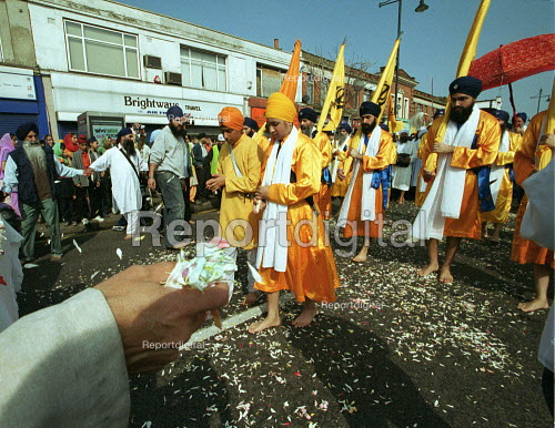 Sikh worshipers at the opening of the new gurdwara Temple in Southall. Worshippers carried a Copy of the Sikh Scriptures, the Guru Granth Sahib, on a Carpet of petals from the old temple to the new. - Duncan Phillips - 2003-03-30