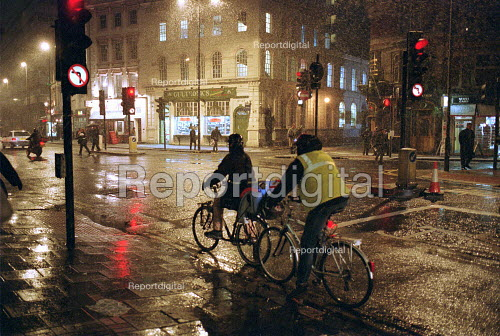 Cyclists in a storm at night West End London - Duncan Phillips - 2003-01-30