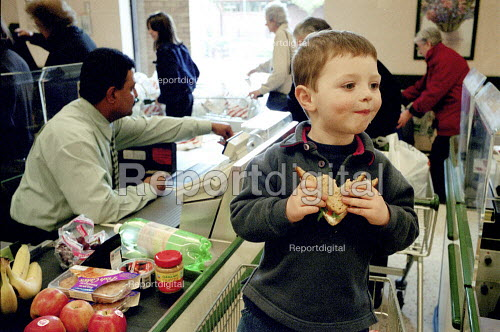 Child at a supermarket checkout eating a sandwich - Duncan Phillips - 2002-11-15