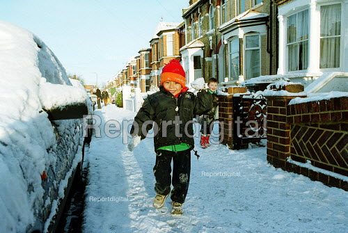 Child throwing a snowball in the snow, London - Duncan Phillips - 2003-01-31
