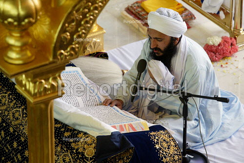 Sikh Holy man reading from the Guru Granth Sahib, also known as the Adi Granth, at the opening of the new gurdwara Temple in Southall, the largest sikh temple in Europe. - Duncan Phillips - 2003-03-30