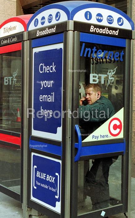 Man using a BT broadband internet phonebox. - Duncan Phillips - 2003-03-05