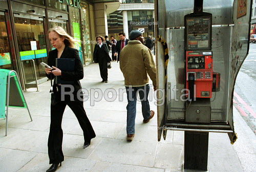 Woman using her mobile phone walks past a vandalised phone booth, City of London - Duncan Phillips - 2003-03-05
