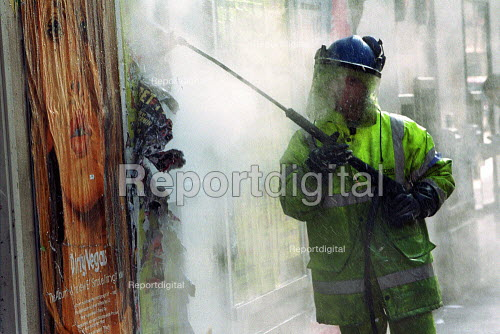 Workman removing illegal fly posters, westminster, using high pressure water jet, as part of a campaign against fly posting & Graffiti. - Duncan Phillips - 2003-03-18