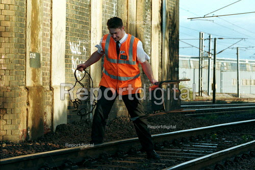 Railway worker on anti vandalism patrol removes debris thrown onto the tracks. This type of vandalism increases during school holiday periods so a dedicated team patrol the tracks to prevent and clear up any danger. - Duncan Phillips - 1999-12-17