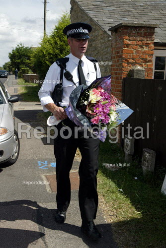 Police Officer delivering flowers outside the Southmoor home of David Kelly the MOD Scientist found dead in a nearby wood. - Duncan Phillips - 2003-07-20