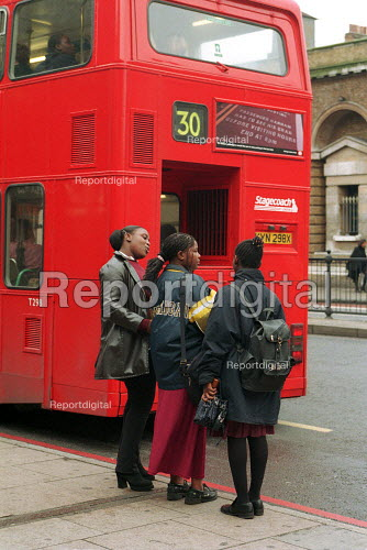 Secondary school children waiting for a bus after school. London - Duncan Phillips - 1999-10-18
